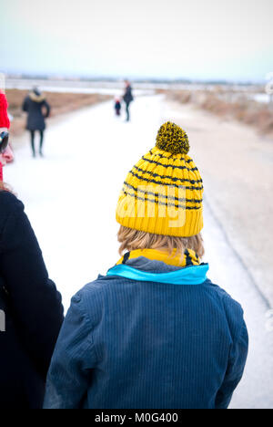 Rear shot of a mother out walking her son with a stripey yellow wooly hat and a worn pinstriped suit jacket. In - Stock Photo