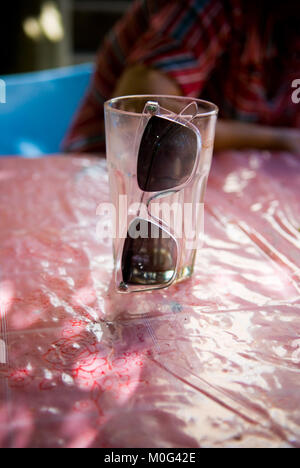 close up of a pair of transparent framed sunglasses hanging off the side of an empty glass on a table with person's - Stock Photo
