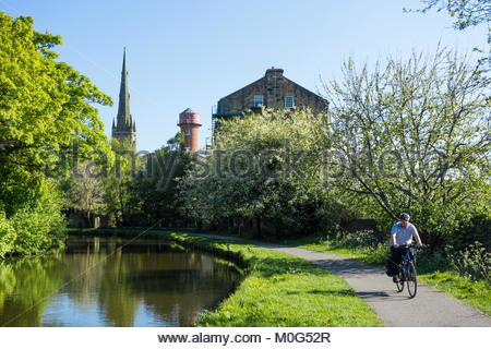 A cyclist on the towpath of the Lancaster Canal, near to White Cross in Lancaster with the distinctive mill water - Stock Photo
