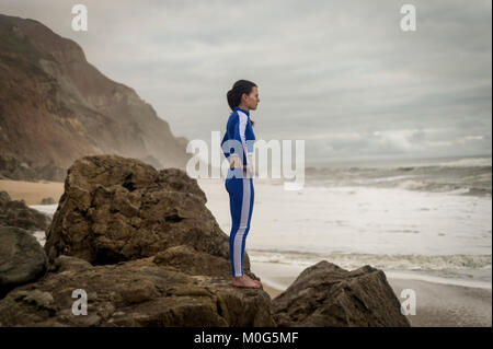 woman standing on rocks watching the surf, wearing blue and white swimwear. Waiting for the surf. - Stock Photo