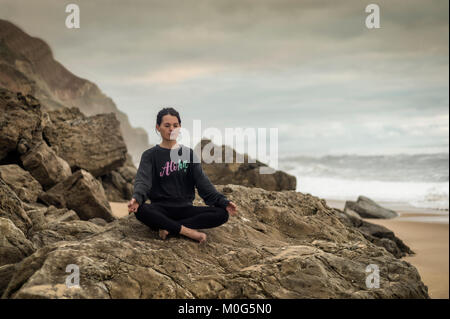 woman doing yoga sitting on a rock by the sea, lotus position. - Stock Photo