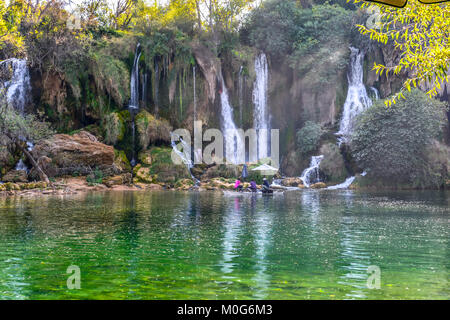 A group of people relax on a raft or boat at Kravica or Kravice Waterfalls on the Trebizat River in the Karstic - Stock Photo