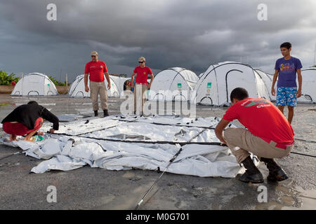 Members of Alegoas Fire Brigade assist in setting up tnets at Uniao Dos Palmares - Stock Photo