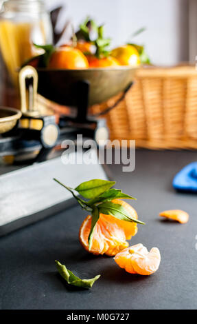 Fresh whole clementines with green leaves in vintage scale and one peeled clementine on a black table with a blue - Stock Photo