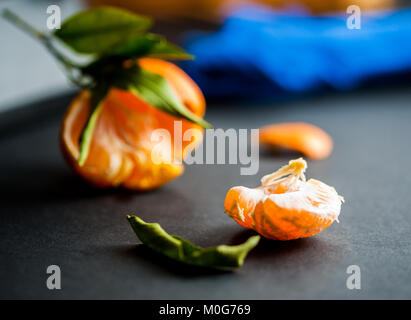 A close-up of a fresh juicy clementines with green leaves - Stock Photo
