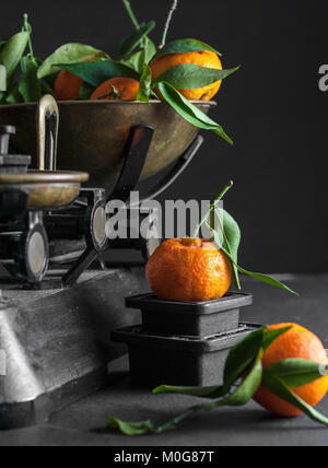 A bunch of fresh juicy clementines with green leaves in a scalepan and on a black table - Stock Photo