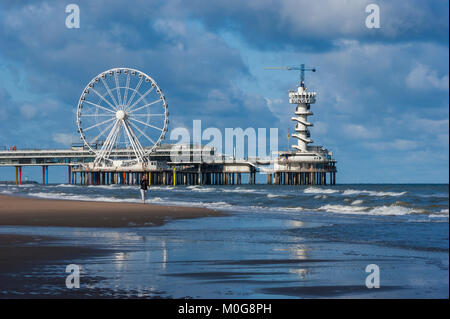 Young woman walking along the beach near Scheveningen Pier and talking on a mobile phone. North Sea beach resort - Stock Photo