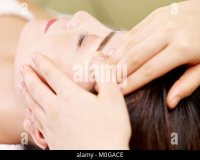 close-up of beautiful young asian woman receiving face massage in spa salon, eyes closed. - Stock Photo