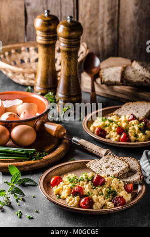 Scrambled eggs with herbs, roasted tomatoes, chive - Stock Photo