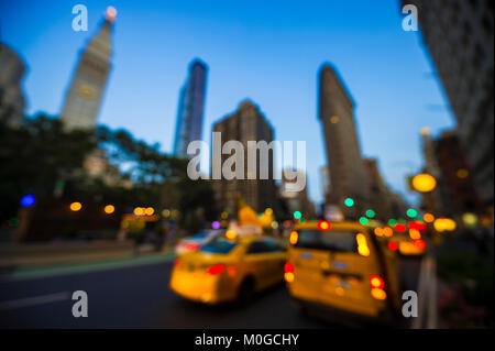 Abstract defocus view of yellow taxis driving through the city streets at dusk in New York City, USA - Stock Photo