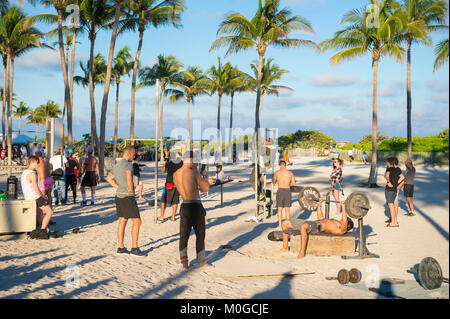 MIAMI - DECEMBER 27, 2017: Muscular young men attract onlookers working out at the outdoor workout station in Lummus - Stock Photo