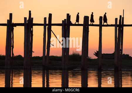 Silhouette of three monks on U-Bein bridge at sunset. Amarapura, Mandalay, Myanmar (Burma). - Stock Photo