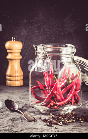 Red hot chilli pepper paprika in glass jar and peppers seed ball and pepper mill on stone table Ingredient for Mexican - Stock Photo