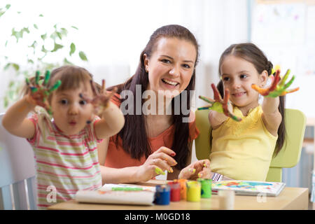 Cheerful children and woman having fun and showing hands painted in colorful paints