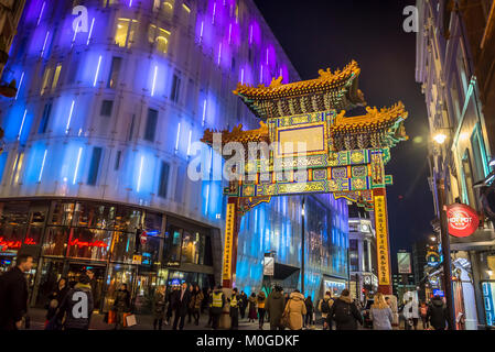 Chinese Arch in colourful Chinatown next to the modern architecture of The Swiss Centre building at night in central - Stock Photo