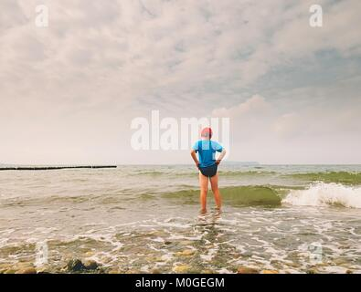 Blond hair boy stay in cold sea tide. Kid on stony beach with foamy waves.  Windy day, cloudy  blue sky on seascape - Stock Photo