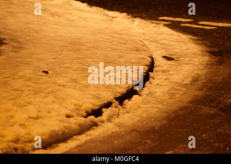 slippery ice and compacted snow covered path under sodium streetlights at night in the uk - Stock Photo