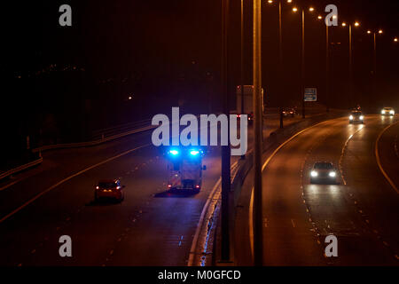 ambulance speeding along motorway with blue lights flashing in northern ireland uk - Stock Photo