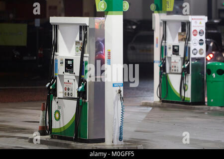 bp garage forecourt with automatic petrol pumps at night in the uk - Stock Photo
