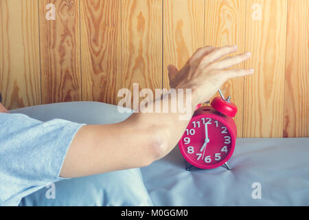 Hand turns off the alarm clock waking up at morning . soft skin tone effect - Stock Photo