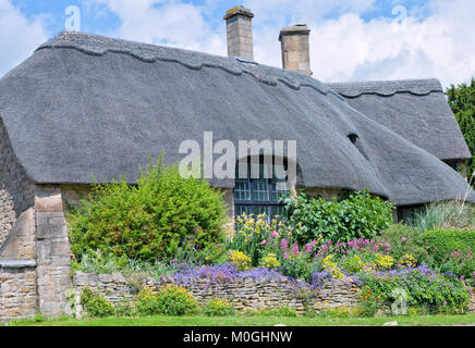 Old traditional English limestone cottage with thatched roof, big window, colourful flowering front garden, on a - Stock Photo