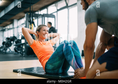 Personal trainer assisting woman lose weight - Stock Photo