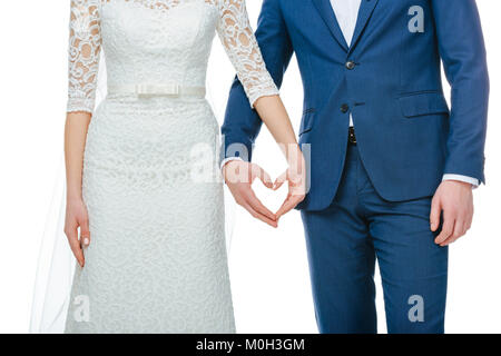 partial view of wedding couple showing heart symbol made of hands together isolated on white - Stock Photo