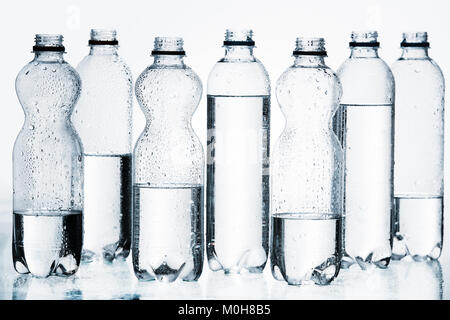 plastic bottles of water in row isolated on white - Stock Photo