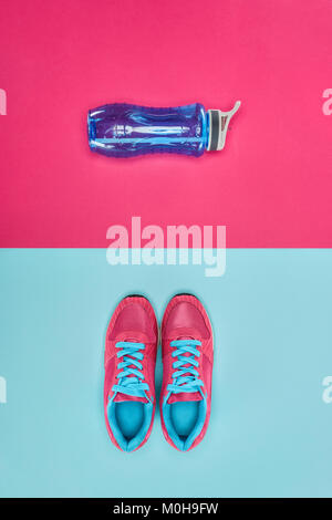 Sports equipment with shoes and water bottle isolated on pink and blue - Stock Photo