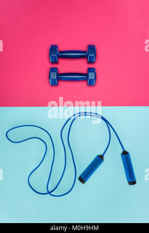Sports dumbbells and skipping rope isolated on pink and blue - Stock Photo