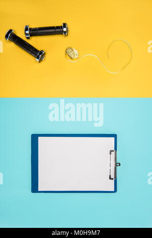 Sports dumbbells, measuring tape and clipboard isolated on yellow and blue - Stock Photo