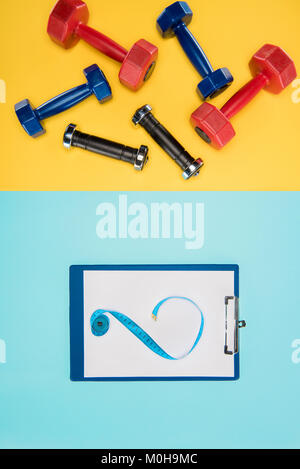 Sports dumbbells and clipboard isolated on yellow and blue - Stock Photo
