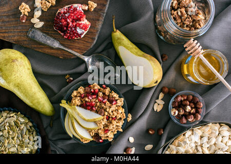 top view of granola ingredients and bowl with granola on table - Stock Photo