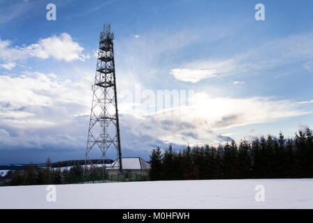 Snowy winter country with transmitters and aerials on telecommunication tower - Stock Photo