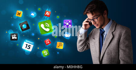 Handsome young man calling by phone with various icons - Stock Photo