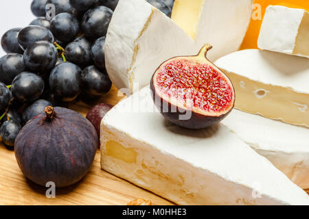 pile of brie or camambert cheese on white background - Stock Photo