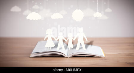 Cardboard figures of the family on opened book. The symbol of unity and happiness - Stock Photo