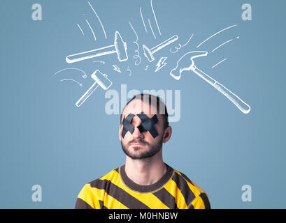 Young man with taped eye and white drawn beating hammer marks around his head - Stock Photo