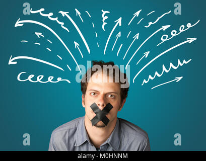 Young man with taped mouth and white drawn lines and arrows around his head - Stock Photo