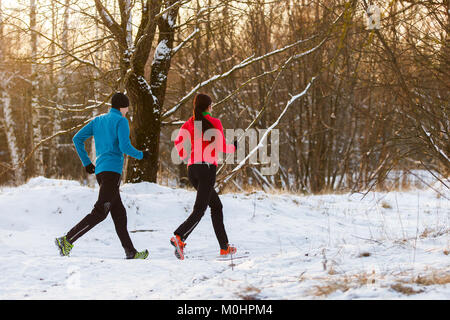Picture from back of sports man and woman on morning run in winter - Stock Photo