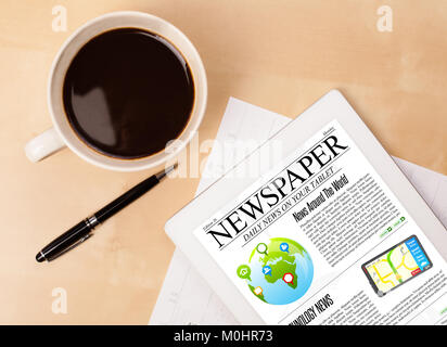 Workplace with tablet pc showing news and a cup of coffee on a wooden work table close-up - Stock Photo