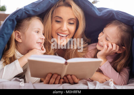 Smiling mom reading a book for her daughters - Stock Photo