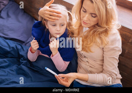 Caring mom taking her daughters temperature - Stock Photo