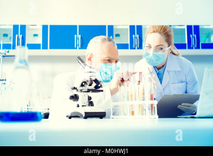 Serious researches conducting experiment in lab - Stock Photo
