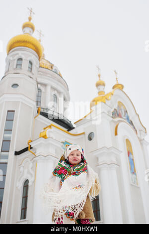 A little girl in a fur coat and a Russian scarf on the background of an Orthodox church - Stock Photo