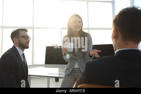colleagues chatting while enjoying coffee break in the office - Stock Photo