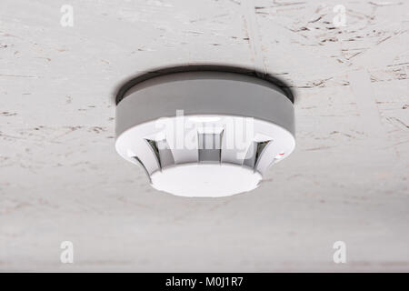 smoke detector of fire alarm on white ceiling at home - Stock Photo