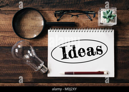 bulb, magnifying glass, glasses, cactus and notebook with IDEAS word on wooden table. ideas concept - Stock Photo