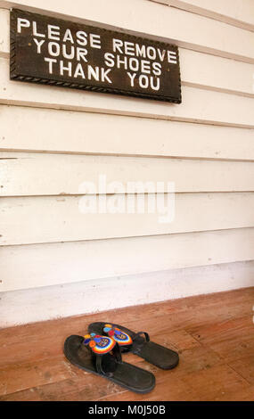 Sign on front porch requesting shoes to be removed - Stock Photo