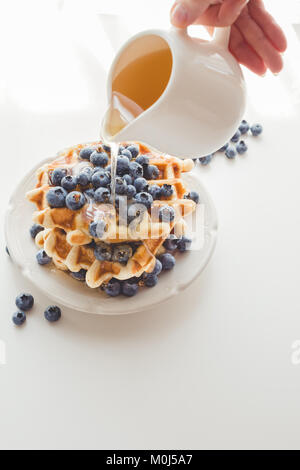cropped shot of woman pouring syrup from saucer on tasty waffles - Stock Photo